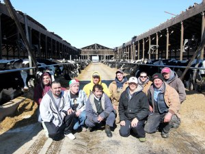 Duane and Marilyn Hershey (front right) can't say enough about how their team of employees pulled together to free cows, restore order and keep 600 cows fed and milked in the hours after the roof collapsed Feb. 14 on about three-quarters of the main freestall barn at Ar-Joy Farms, Cochranville, Pa . They are pictured here with adaptable bovines eating TMR calmly under the open sky behind them three days later on Feb. 17